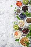 Здоровая еда фитнеса от свежих фруктов, ягод, зеленых цветов, супер еды: kinoa, семена chia, семя льна, клубника, голубика Стоковые Изображения RF