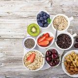 Здоровая еда фитнеса от свежих фруктов, ягод, зеленых цветов, супер еды: kinoa, семена chia, семя льна, клубника, голубика Стоковое Изображение RF