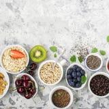 Здоровая еда фитнеса от свежих фруктов, ягод, зеленых цветов, супер еды: kinoa, семена chia, семя льна, клубника, голубика Стоковое фото RF