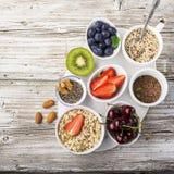 Здоровая еда фитнеса от свежих фруктов, ягод, зеленых цветов, супер еды: kinoa, семена chia, семя льна, клубника, голубика Стоковая Фотография