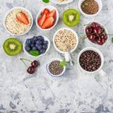 Здоровая еда фитнеса от свежих фруктов, ягод, зеленых цветов, супер еды: kinoa, семена chia, семя льна, клубника, голубика Стоковая Фотография RF