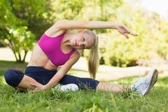 Здоровая и красивая женщина делая протягивающ тренировку в парке Стоковое Фото