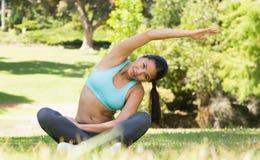 Здоровая и красивая женщина делая протягивающ тренировку в парке Стоковые Изображения