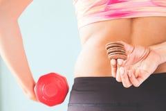 Здоровая концепция образа жизни, диета и фитнес, закуска фитнеса женская держа и гантель в другой руке Стоковое Изображение RF