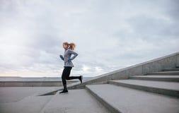 Здоровая молодая женщина бежать вниз с шагов Стоковое Изображение