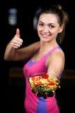 Здоровая молодая женщина есть салат овощей зеленый на темном спортзале стоковое изображение rf