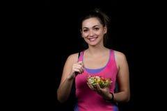 Здоровая молодая женщина есть салат овощей зеленый на темном спортзале стоковая фотография