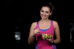Здоровая молодая женщина есть салат овощей зеленый на темном спортзале стоковая фотография rf