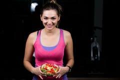 Здоровая молодая женщина есть салат овощей зеленый на темном спортзале стоковое фото rf