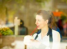 Здоровая молодая женщина наслаждаясь ее smoothie в баре сока стоковая фотография