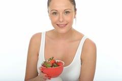 Здоровая молодая женщина пригонки держа шар свежих зрелых сочных клубник Стоковые Фото