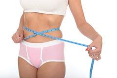 Здоровая молодая женщина проверяя ее потерю веса с рулеткой Стоковое Фото