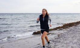 Здоровая молодая женщина jogging на пляже стоковая фотография rf