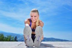 Здоровая молодая милая женщина протягивая ее ногу во время тренировки в парке стоковые изображения
