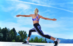 Здоровая молодая милая женщина протягивая ее ногу во время тренировки в парке Стоковые Изображения RF
