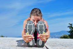 Здоровая молодая милая женщина протягивая ее ногу во время тренировки в парке Стоковое Изображение RF