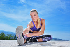 Здоровая молодая милая женщина протягивая ее ногу во время тренировки в парке Стоковое Фото