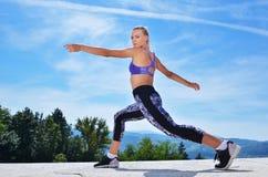 Здоровая молодая милая женщина протягивая ее ногу во время тренировки в парке Стоковое фото RF