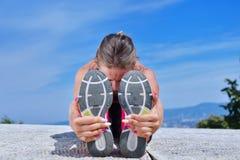 Здоровая молодая милая женщина протягивая ее ногу во время тренировки в парке Стоковая Фотография