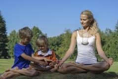 Здоровая семья делая йогу в парке Стоковые Фотографии RF