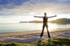 Здоровая счастливая женщина наслаждаясь солнечным утром на пляже