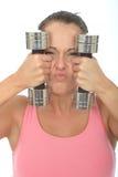Здоровая шальная молодая женщина держа тупые весы колокола и вытягивая придурковатое выражение лица Стоковая Фотография RF
