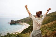 Здоровое ликование женщины перед ландшафтом вида на океан стоковые фото