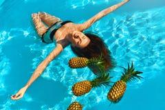 Здоровое питание, питание Женщина с ананасами в бассейне (вода) стоковые фото