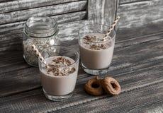 Здоровое питье - smoothie банана и овсяной каши в стекле на темной деревянной предпосылке Стоковые Фото