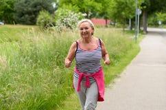 Здоровой женщина постаретая серединой Jogging на улице стоковое фото