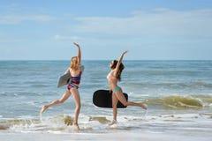 Здоровые атлетические подруги серфера при тела пригонки держа доски Стоковая Фотография RF