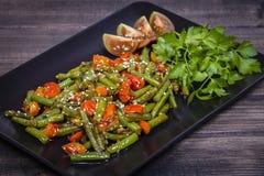 Здоровые зеленые фасоли, красный томат вишни с семенами сезама Стоковая Фотография