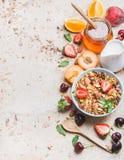 Здоровые ингридиенты завтрака Granola овса в шаре с листьями гаек, клубники и мяты, кувшином, медом в опарнике, свежем стоковые изображения rf