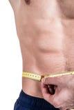 Здоровые образ жизни и фитнес Красивый парень sportive, размер талии измерений, изолированный на белой предпосылке Горизонтальная Стоковые Изображения RF