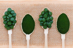 Здоровые образ жизни, superfood, морская водоросль, spirulina и пилюльки и порошок хлореллы в деревянных ложках Стоковые Фото