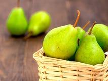 Здоровые органические груши в корзине на деревянном столе Стоковые Изображения