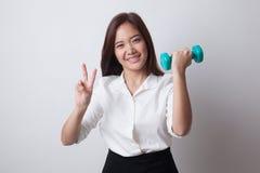 Здоровый азиатский знак победы выставки бизнес-леди с гантелями Стоковая Фотография