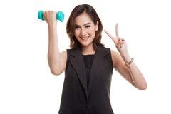 Здоровый азиатский знак победы выставки бизнес-леди с гантелями Стоковая Фотография RF