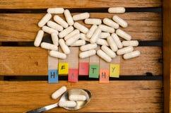 Здоровый алфавит и лекарство и ложка капсулы на деревянной предпосылке стоковое фото