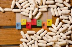 Здоровый алфавит и капсула дают наркотики на деревянной предпосылке стоковые фото