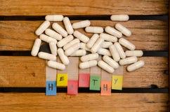 Здоровый алфавит и капсула дают наркотики на деревянной предпосылке стоковое фото rf