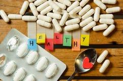 Здоровый алфавит и капсула дают наркотики с меньшим красным сердцем на деревянной предпосылке стоковое изображение rf
