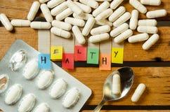 Здоровый алфавит и капсула дают наркотики с ложкой на деревянной предпосылке стоковое изображение