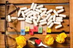 Здоровый алфавит и капсула дают наркотики с стеклами и красным сердцем на деревянной предпосылке стоковое фото rf
