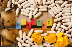 Здоровый алфавит и капсула дают наркотики с стеклами на деревянной предпосылке стоковые фотографии rf