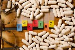Здоровый алфавит и капсула дают наркотики с стеклами на деревянной предпосылке стоковое изображение rf