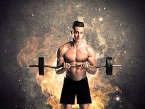Здоровый горячий мужчина показывая мышцы с огнем Стоковое фото RF