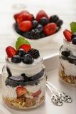Здоровый десерт югурта с muesli, клубниками, ежевиками и голубиками на белом деревянном столе Стоковая Фотография RF