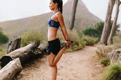 Здоровый женский бегун протягивая ноги на горной тропе Стоковое Фото