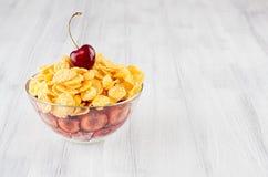 Здоровый завтрак в шаре с золотыми хлопьями мозоли, зрелой вишне куска на белой деревянной доске Стоковые Фотографии RF
